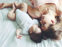 Portrait of beautiful mom playing with her 4 months old baby in